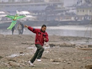 A young Chinese boy flies a kite